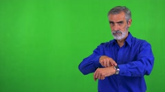 Old senior man points on watch (show time) - green screen - studio Stock Footage