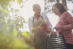 Nursery plant worker showing potted flowers to woman Stock Photos