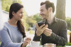 Couple with cell phone drinking coffee at outdoor cafe Stock Photos