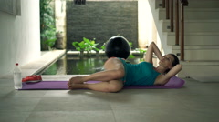 Young woman doing stomach exercise on floor on mat in luxury villa,4K Stock Footage