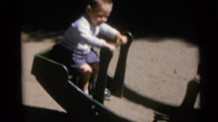 1967: two children have fun on a piece of playground equipment CAMDEN Stock Footage