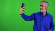 Old senior man photographs with smartphone (selfie) - green screen - studio Stock Footage