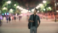 Tourist takes photo on the smartphone is an interesting place, the city at night Stock Footage