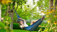 Young woman talking on the phone while lying in a hammock. HD Stock Footage