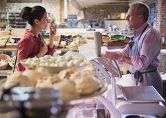 Deli worker offering cheese sample to woman in market Stock Photos