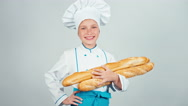 Baker girl 7-8 years child holds bread baguettes and smiling at camera Stock Footage