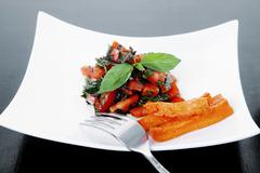 Vegetable salad : cherry tomatoes and basil with sweet baked pot Stock Photos