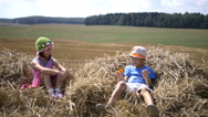 Boy gives flower to the girl, boy with girl sitting on the hay on the mountain Stock Footage