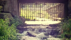 Creek flowing throught old gate Stock Footage