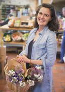 Portrait smiling woman with flowers in basket shopping in market Stock Photos