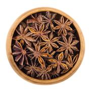 Star anise seeds in a wooden bowl over white Stock Photos