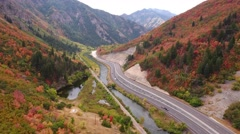 Aerial shot of cars driving on mountain highway with fall colors Stock Footage