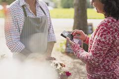 Plant nursery worker waiting as woman uses credit card machine Stock Photos