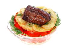 Roast beef meat chunk in transparent bowl over baked potatoes Stock Photos