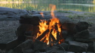 Campfire at campsite. Defocused lake and trees in the background. Stock Footage