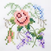 Flowers motif hand embroidery on white linen tablecloth Stock Photos