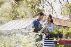 Plant nursery workers with clipboard and potted plants in sunny garden Stock Photos