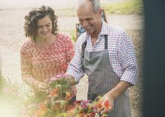 Plant nursery worker helping woman with flowers Stock Photos