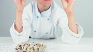 Close up portrait chef cook girl holding two quail eggs and smiling at camera Stock Footage