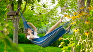 The girl in a hammock. He is talking on the phone and smiling. HD Stock Footage