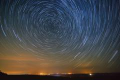 Trail stars around Polar Star the glowing over city. Stock Photos