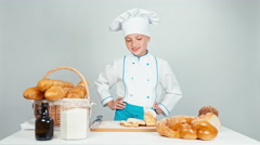Baker girl standing near kitchen table with bakery products and smiling Stock Footage