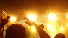 Silhouettes of concert crowd in front of bright stage lights, visible noice f Stock Footage