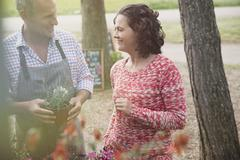 Plant nursery worker helping woman with potted flowers Stock Photos