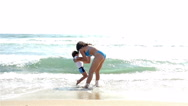 Mother and little son playing with sea waves, slow motion Stock Footage