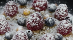 Cake with raspberries, blueberries, sea buckthorn sprinkled rotates Stock Footage