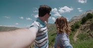 Young couple in the mountains, enjoy the nature and a carefree life, taking Stock Footage