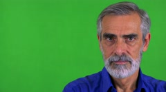 Old senior man looks to camera with serious face - green screen - studio Stock Footage