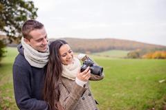 Beautiful young couple with camera taking pictures. Autumn natur Stock Photos