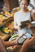 Woman watching grocery store clerk using credit card machine Stock Photos