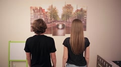 Boy and girl looking at a picture on the wall Stock Footage