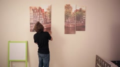 Boy and girl hanging a picture on the wall Stock Footage