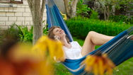 Beautiful girl lying in a hammock. He is talking on the phone and laughing. HD Stock Footage