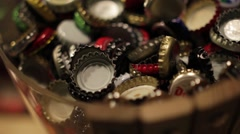 Beer Bottle Caps Thrown Into a Bowl Stock Footage