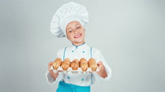 Chef cook girl 7-8 years holding tray of egg Stock Footage