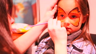 Face painting. Woman artist painting face of little girl Stock Footage