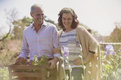 Smiling couple shopping for flowers in sunny plant nursery garden Stock Photos