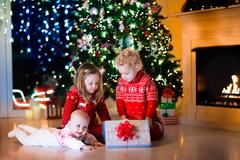 Kids opening Christmas presents at fireplace Stock Photos