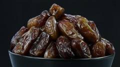 Dried date fruit in a black plate rotates on a black background, close up Stock Footage