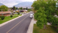 Aerial shot of tree and road in mountain city suburb Stock Footage