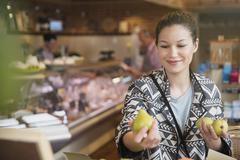Smiling woman examining pears in market Stock Photos