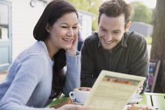 Smiling couple reading menu at outdoor cafe Stock Photos