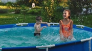 Boy and Girl Splash in the Pool in the Garden Stock Footage