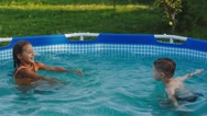 Happy Brother and Sister Splash in the Pool Stock Footage
