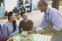 Waiter serving cappuccinos to smiling couple an outdoor cafe Stock Photos