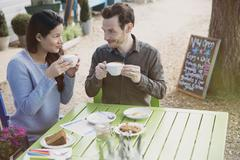 Couple enjoying cappuccinos and dessert an outdoor cafe Stock Photos